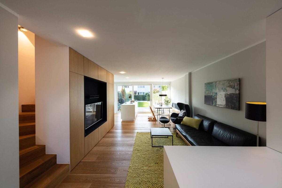 Blick auf den Wohnbereich und das hochwertige Einbaumöbel mit Tip-On-Beschlägen im Einfamilienhaus KLE - Der durchgesteckte Grundriss ermöglicht das sog.