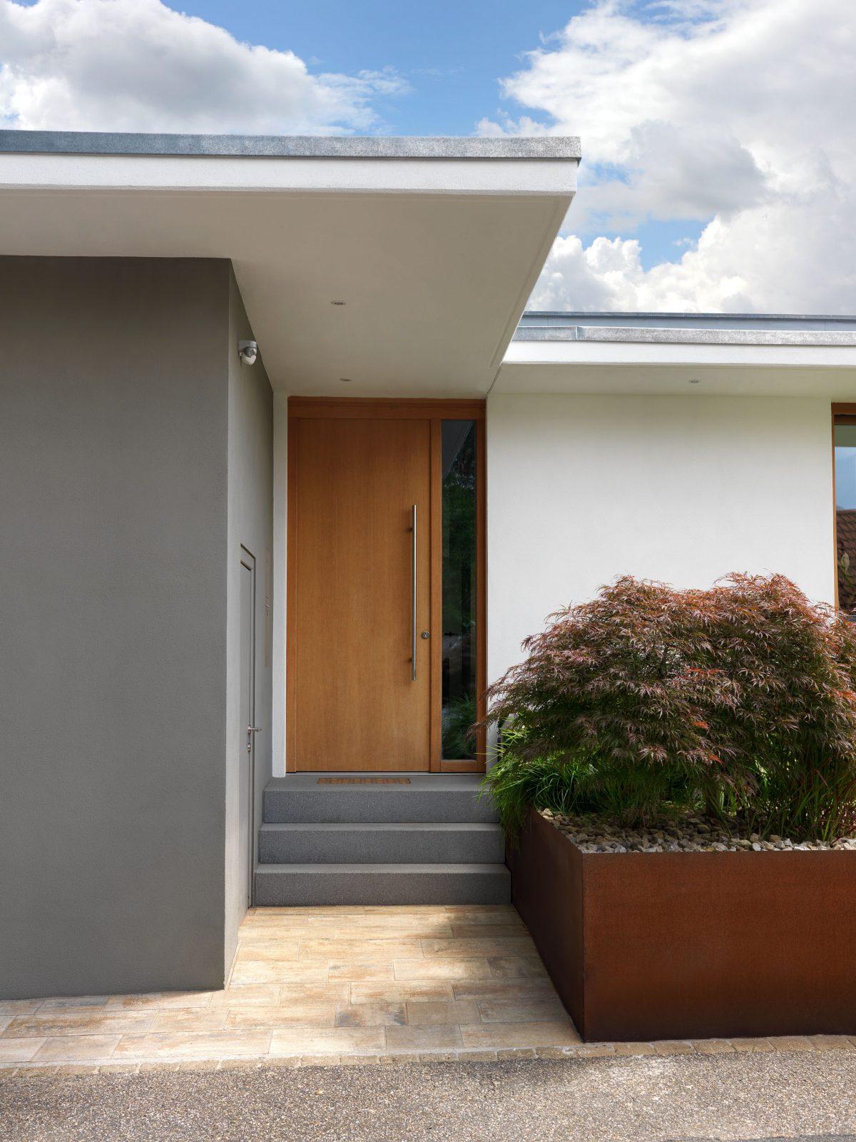 Blick auf den Eingangsbereich des Hauses BRM mit Pflanzkübel aus Cortenstahl.