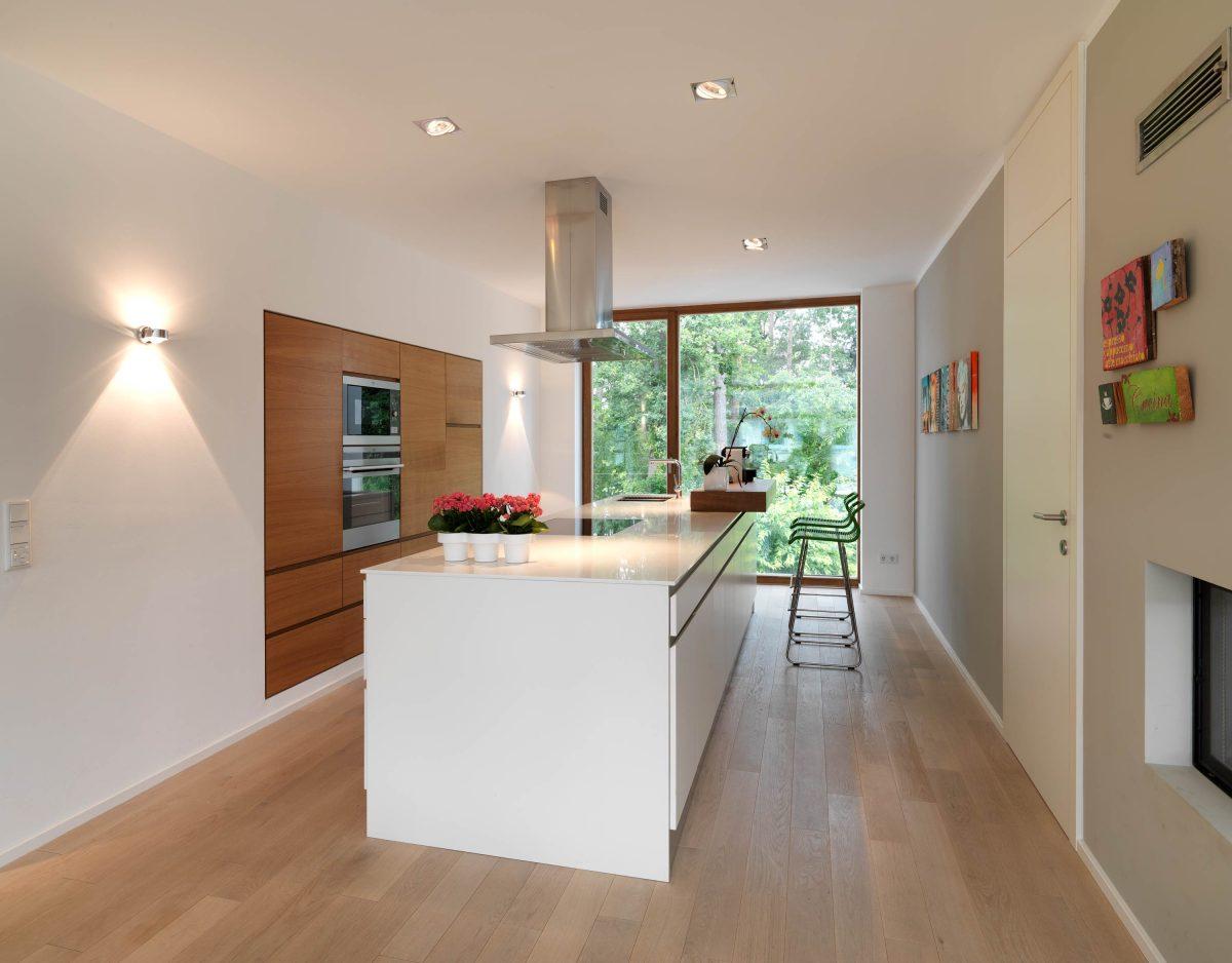 Die Kuecheninsel mit Block Ablage für die Barhocker und integrierte Kuechenzeile im Einfamilienhaus