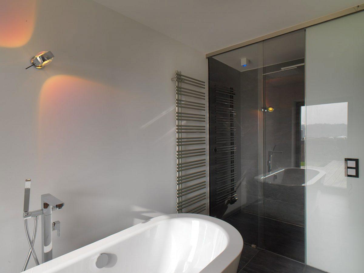 Die freistehende Badewanne im Haus KMH mit Blick auf den durch Glas-Schiebeelemente abgetrennten Duschbereich mit Duschhimmel.