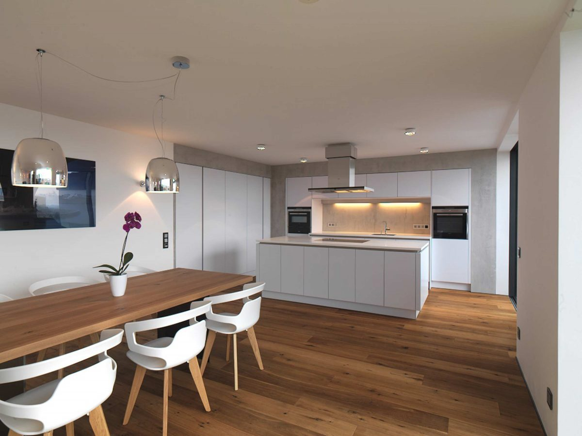 Der Ess- und Kochbereich mit separater Kochinsel und in die Wand integrierten Kuechenzeilen im Einfamilienhaus