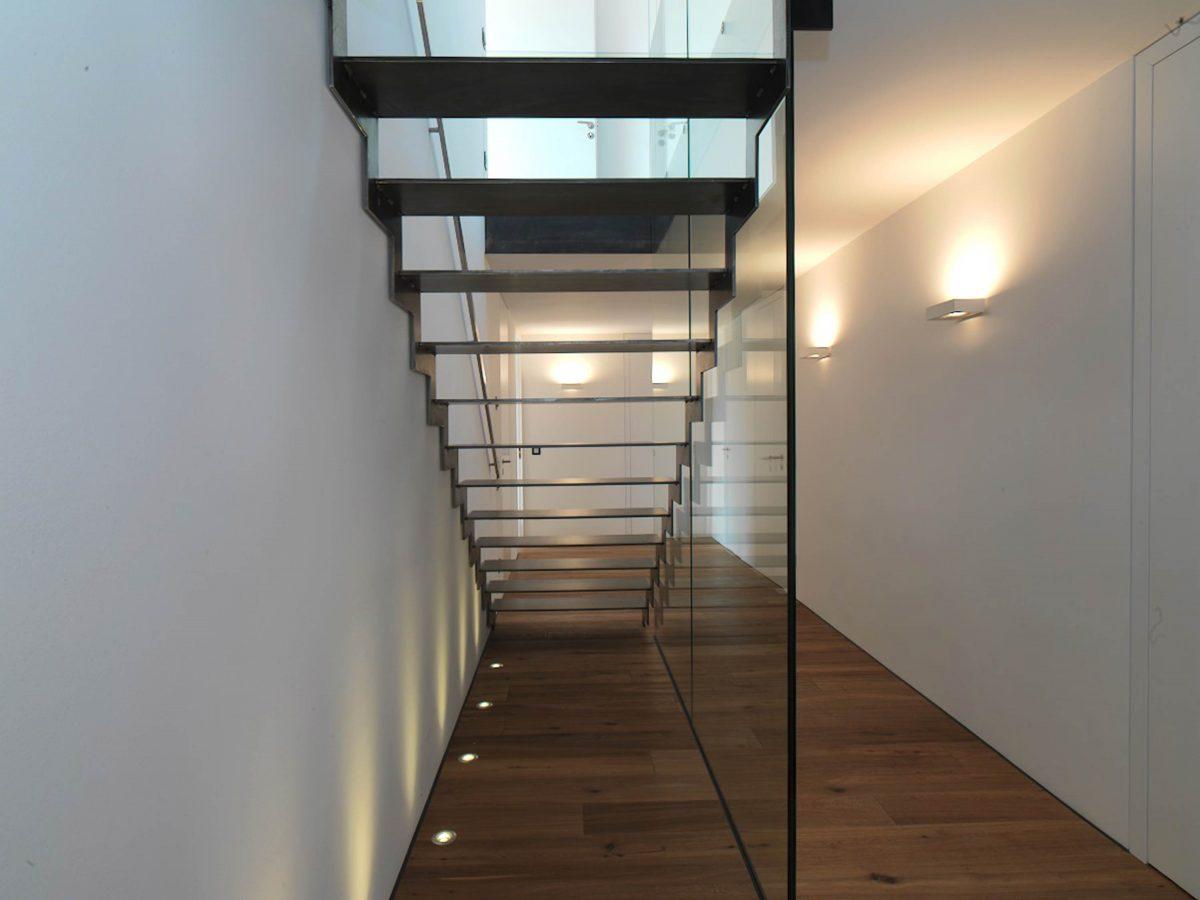 Die neue freitragende Stahltreppe mit Stufen aus geflammten Stahl und Bodenstrahlern im Einfamilienhaus