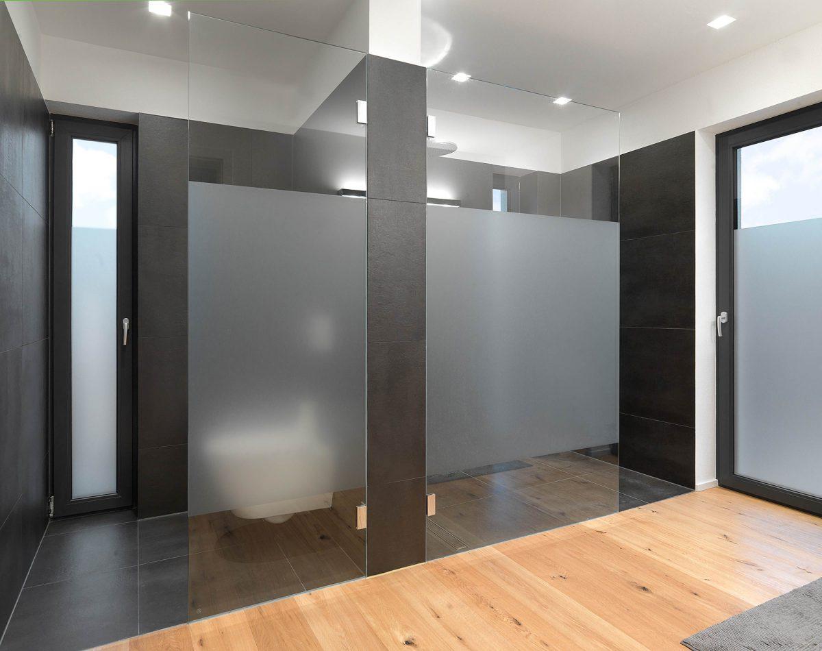 Der Dusch- und WC Bereich mit anthrazitfarbenen Fliesen und hellem Echtholzfußboden im Bad von Einfamilienhaus