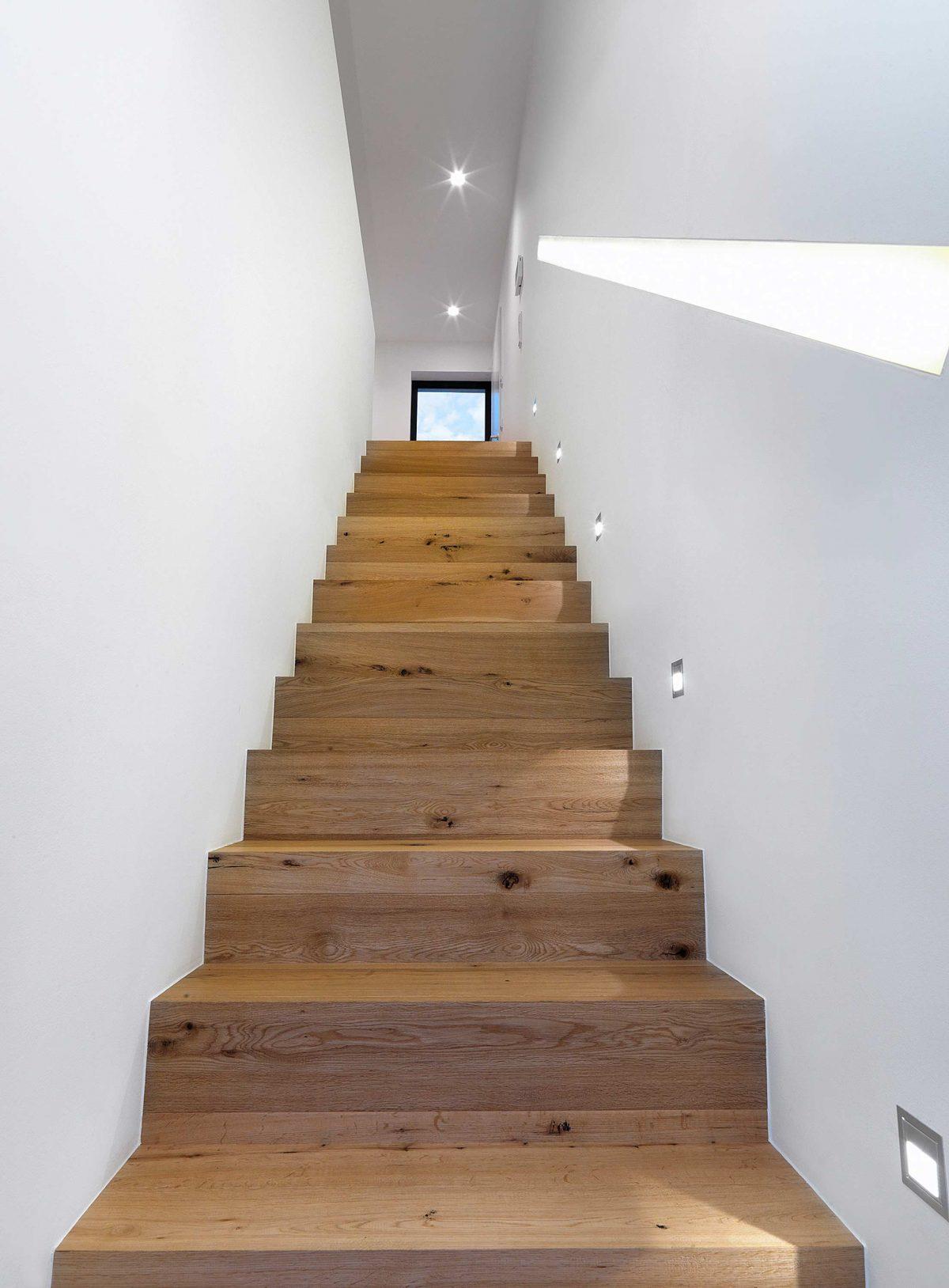 Die gerade Treppe mit Echtholzverkleidung und abschnittsweisen LED-Strahlern im Einfamilienhaus