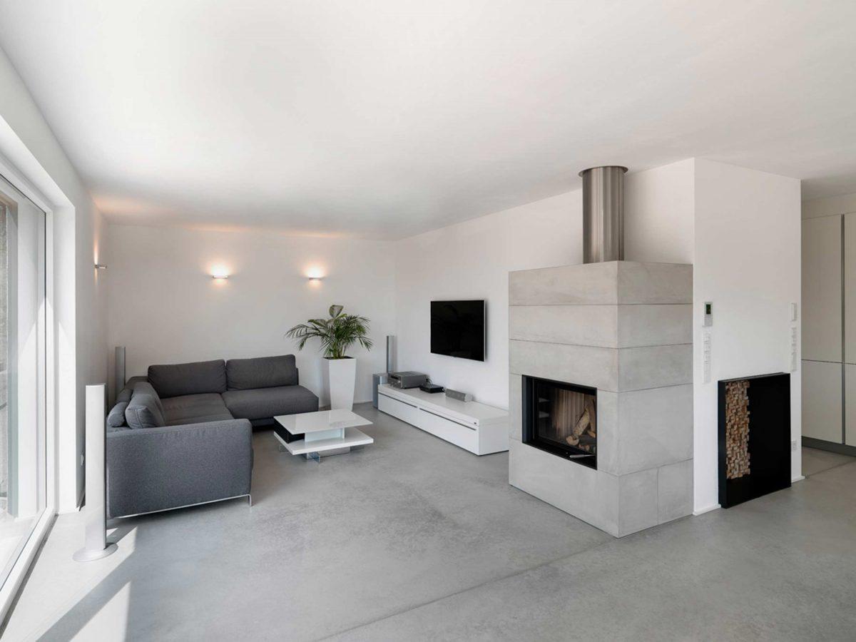 Der Wohnbereich mit Sichtbeton-Kamin und fluegelgeglaettetem Estrich im Einfamilienhaus