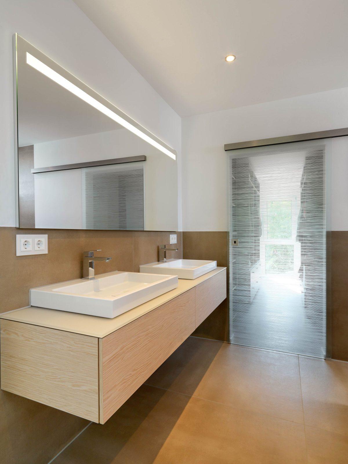 Der Waschtisch im Badezimmer der Eltern im Einfamilienhaus RSO mit Zugang zum begehbaren Kleiderschrank.