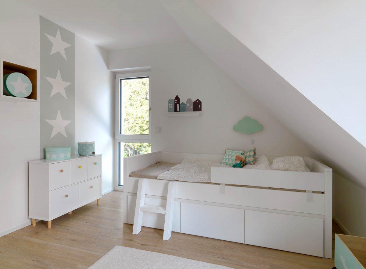 Blick ins Kinderzimmer des Einfamilienhauses - der hell gestaltete Raum bekommt einige Blickpunkte durch die mint-farbenen Akzente der Accessoires.