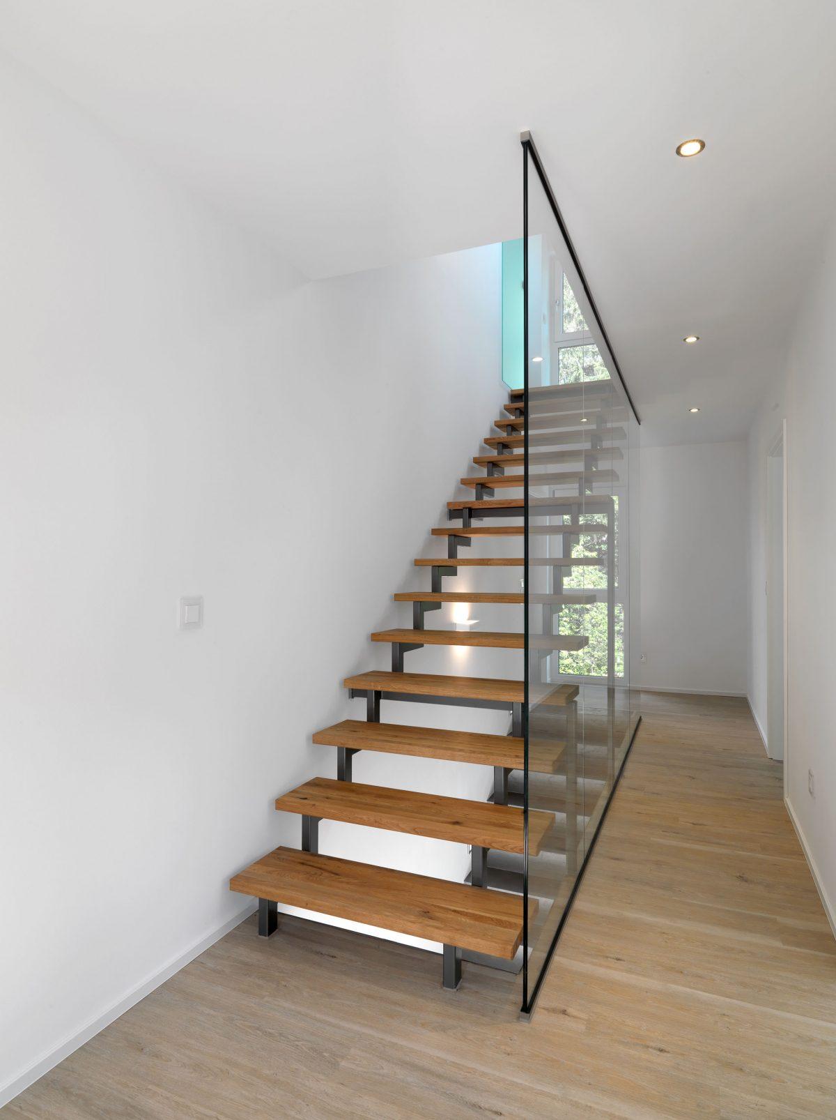 Die setzstufenlose gerade Treppe auf zwei Stahlholmen abgetrennt vom Flur durch feste Glaselemente.