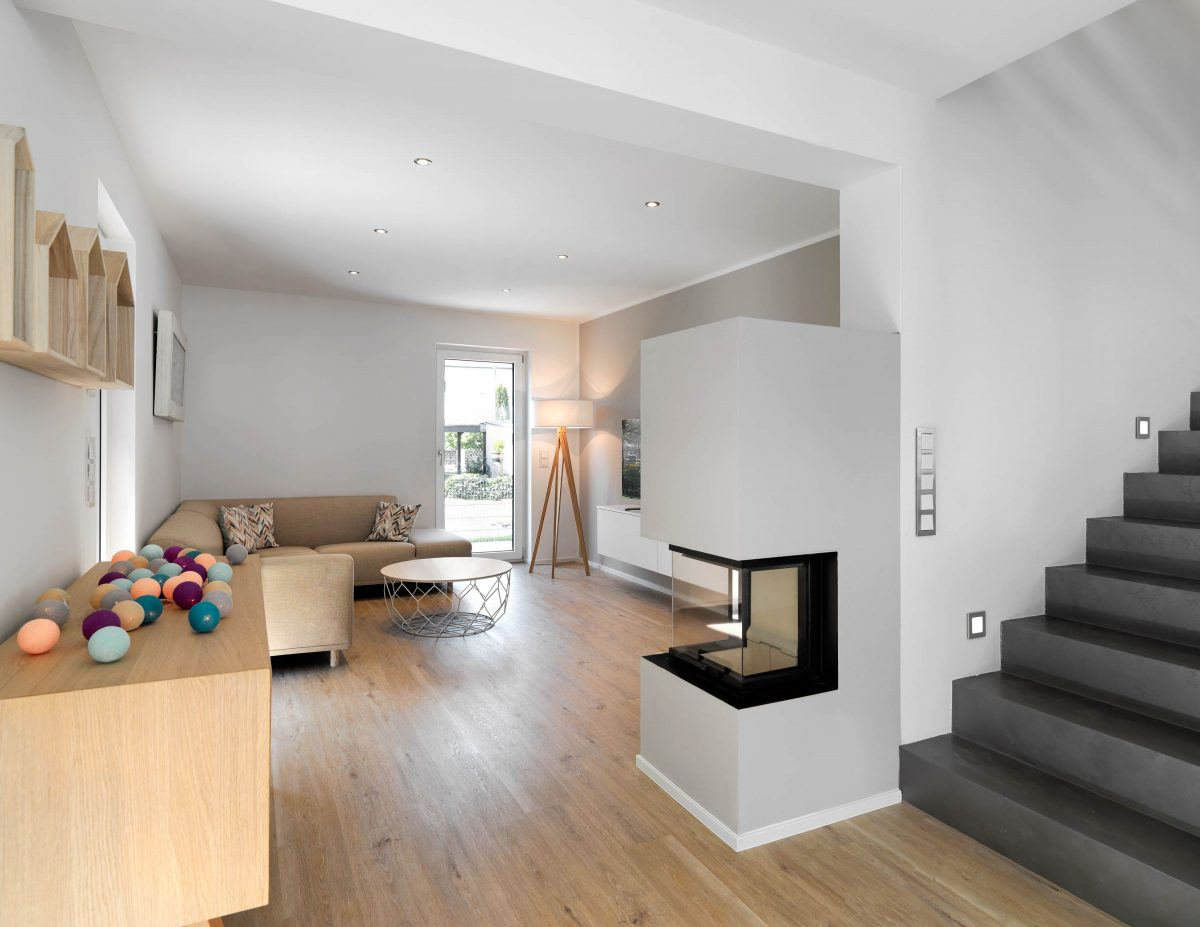 Blick in den Wohnbereich mit 3-seitigen Panorama Kamin im Einfamilienhaus