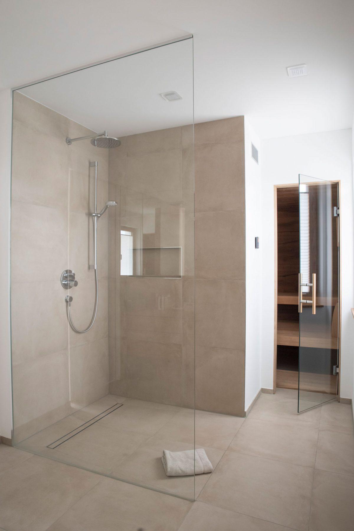 Walk-In Duschbereich im Wellness Bereich des Hauses WEL mit bodengleichem Abflusssystem und runder Regenwald-Brause.