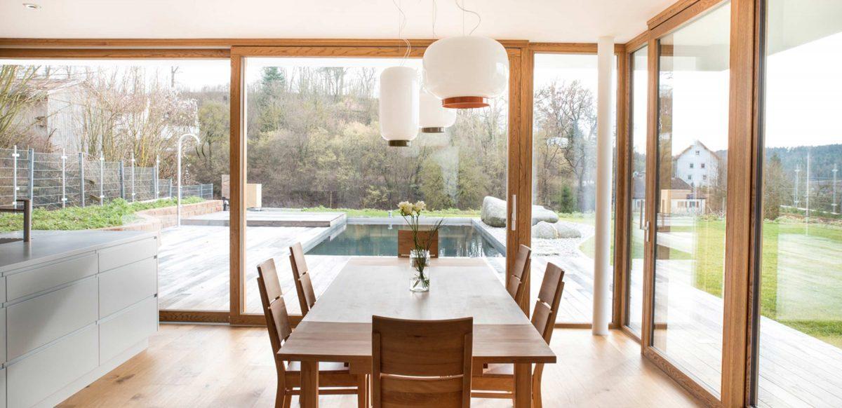 Blick auf den Essbereich des Einfamilienhauses WEL mit Über-Eck-Verglasung und Hebeschiebetüren. Der komplett verglaste Essbereich geniesst den Blick auf Terrasse und Garten inklusive Pool.