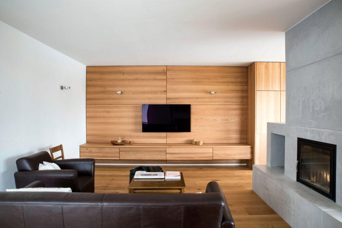 Wohnbereich des Hauses WEL mit Sitzbeton-Kamin als Raumtrenner und Holzvertäfelung als Blickfang.