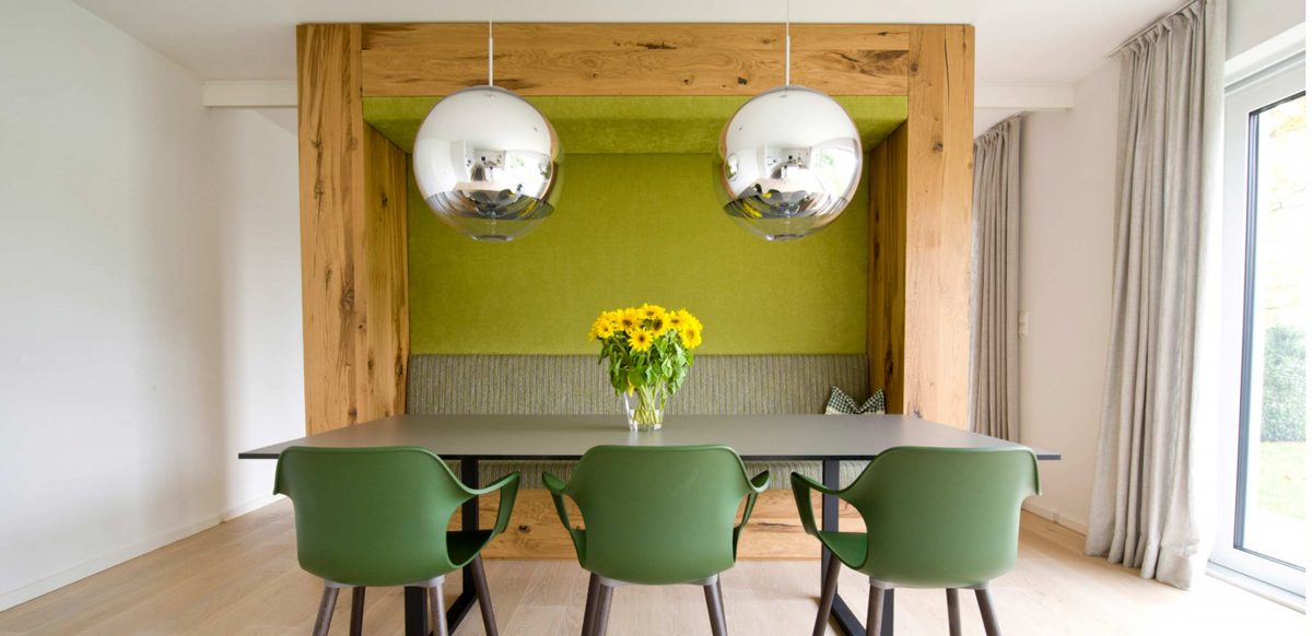Blick auf den Essbereich mit waldgrünen Akzenten und Einbaumöbel mit Sitznische in der Villa