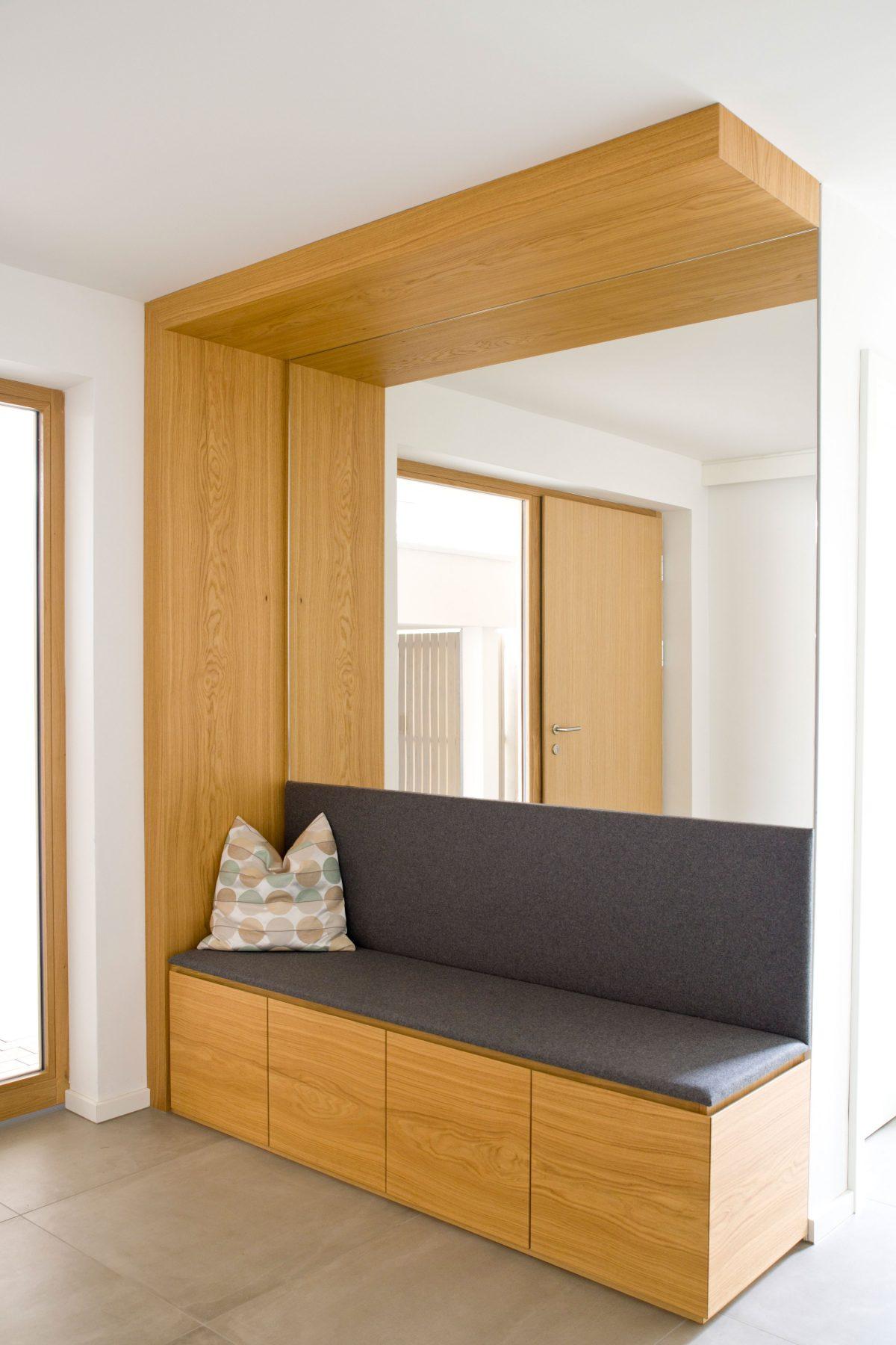 Das multifunktionale Sitzmöbel im Eingangsbereich mit passgenauer Spiegelwand.