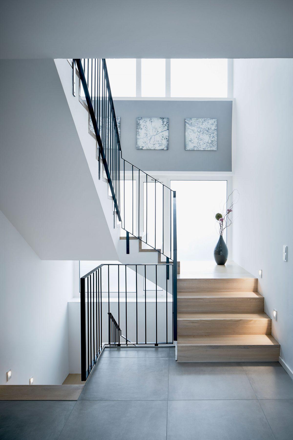 Die sanierte Treppe in der Villa BYR mit neuen Tritt- und Setzstufen aus Holz und neuem Geländer sowie eine abschnittsweise LED Wandeinbauleuchten.
